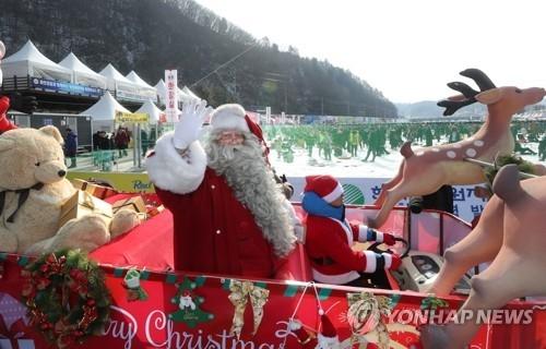 """资料图片:1月13日,在江原道华川郡,来自芬兰的""""圣诞老人""""驾着""""驯鹿""""周游鳟鱼节现场。(韩联社)"""