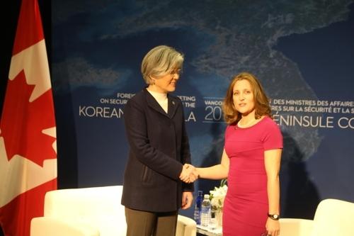 1月15日,在温哥华会议中心,韩国外长康京和(左)和加拿大外长弗里兰在双边会谈前握手。(韩联社)