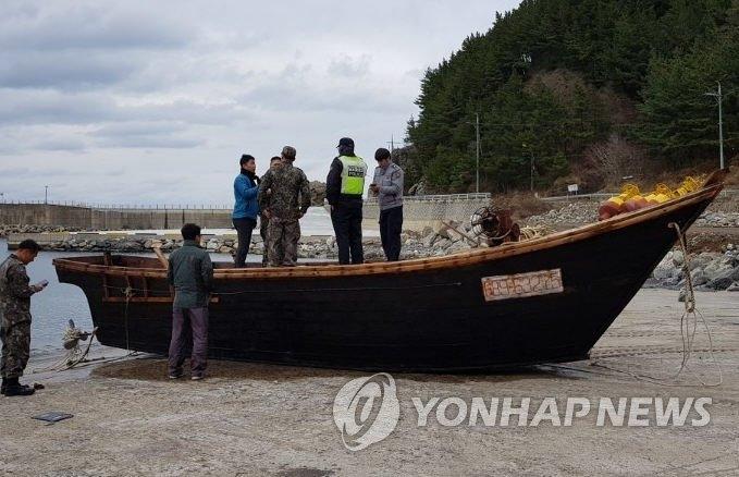 资料图片:1月7日上午,在庆尚北道郁陵郡以北海域,韩国渔民在海上发现一艘载有4具疑似朝鲜居民尸体的小木船。图为韩国海警等有关人员将船只拖往玄圃港后调查情况。(韩联社)