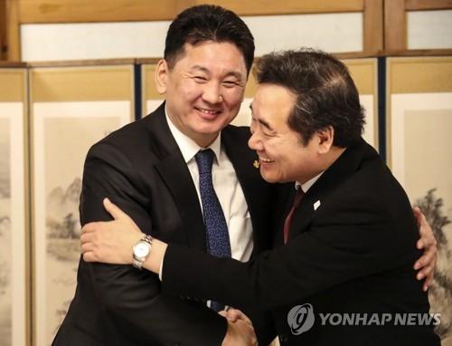 1月16日晚,在首尔三清洞总理公馆,韩国国务总理李洛渊(右)同蒙古国总理呼日勒苏赫在欢迎晚宴上拥抱问候。(韩联社)