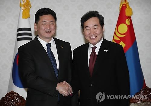 1月16日下午,在首尔政府大楼,韩国国务总理李洛渊(右)同蒙古国总理握手合影。(韩联社)