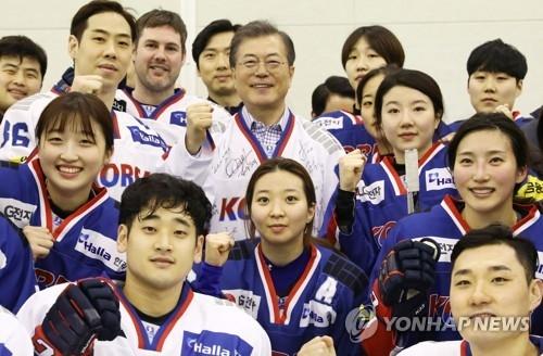 1月17日上午,在忠清北道镇川选手村,文在寅与韩国冰球队运动员们合影。(韩联社)
