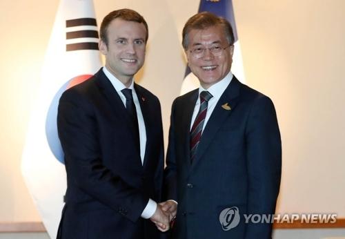 资料图片:当地时间7月8日下午,韩国总统文在寅(左)与法国总统马克龙在德国汉堡会面,两人握手。(韩联社)