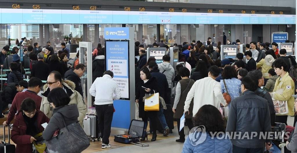资料图片:1月18日下午,在仁川机场第二航站楼,游客等待值机。(韩联社)