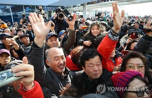 1月21日,在江陵火车站,市民向朝鲜艺术团先遣队一行挥手。(韩联社)
