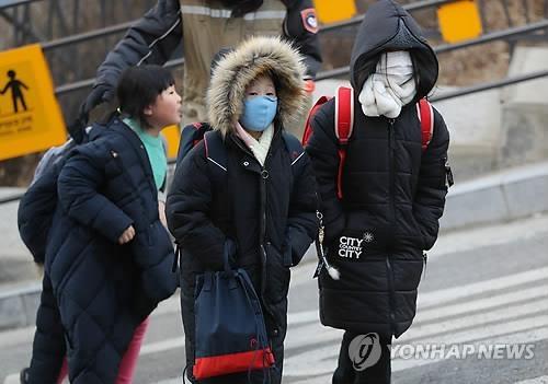 1月24日上午,最强寒潮来袭,图为在首尔玉水洞,迎来开学的小学生们在寒潮中去上学。(韩联社)