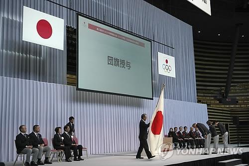 1月24日,在东京,日本奥委会主席竹田恒和向平昌冬奥日本体育代表团授予团旗。(韩联社)
