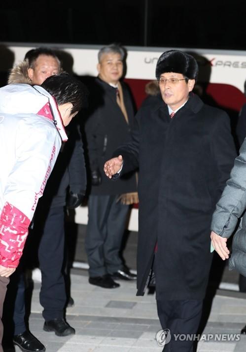 1月25日晚,在江陵市关东冰球中心,尹勇福与韩方奥组委接待人员握手。(韩联社)