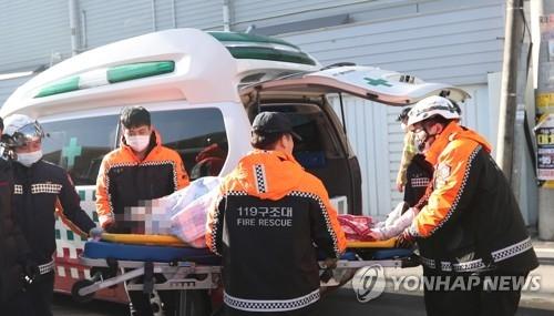 1月25日,在密阳市世宗医院火灾现场,消防人员搬运遇难者遗体。(韩联社)