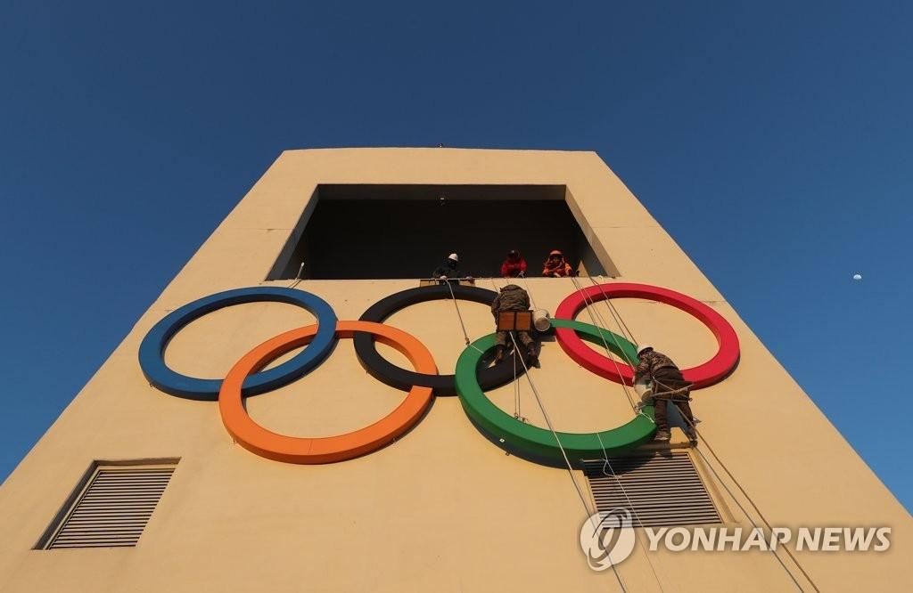 资料图片:1月27日,在江原道平昌郡阿尔卑希亚奥林匹克公园,在距离2018平昌冬奥会开幕仅有13天之际,高空作业人员在安装奥运五环标志。(韩联社)