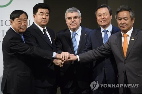 资料图片:当地时间1月20日,韩朝与国际奥委会有关朝鲜参奥的会谈在瑞士洛桑举行,国际奥委会主席巴赫(中)与韩朝双方代表握手。(韩联社)