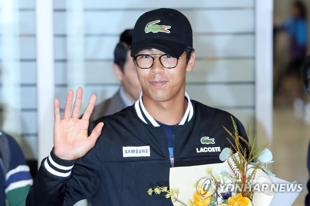1月28日晚,在仁川国际机场,韩国网球运动员郑泫向欢迎人群挥手致意。(韩联社)