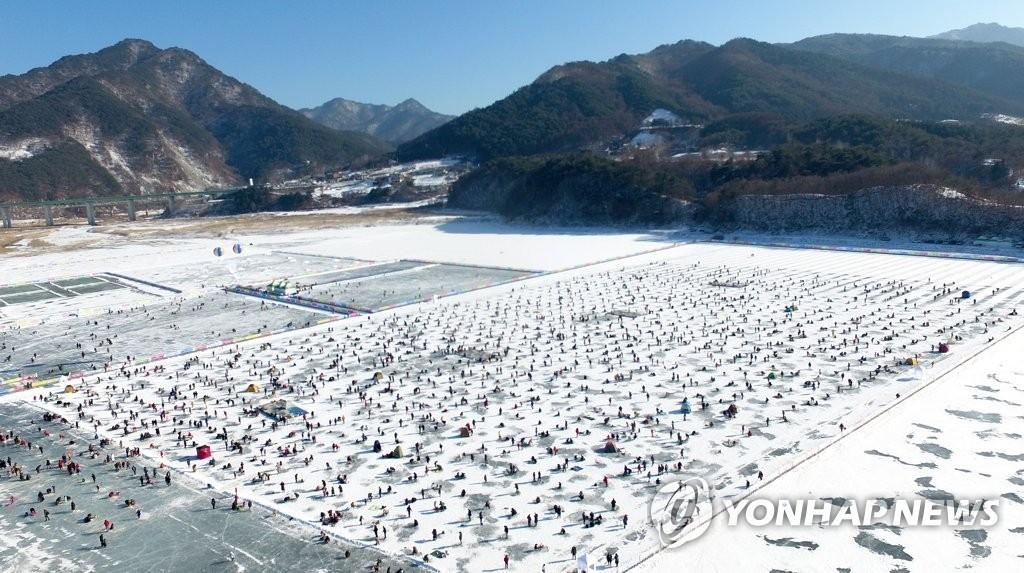 1月27日,江原道麟蹄郡,麟蹄冰鱼节开幕当天大批游客体验冰上钓鱼。(韩联社)