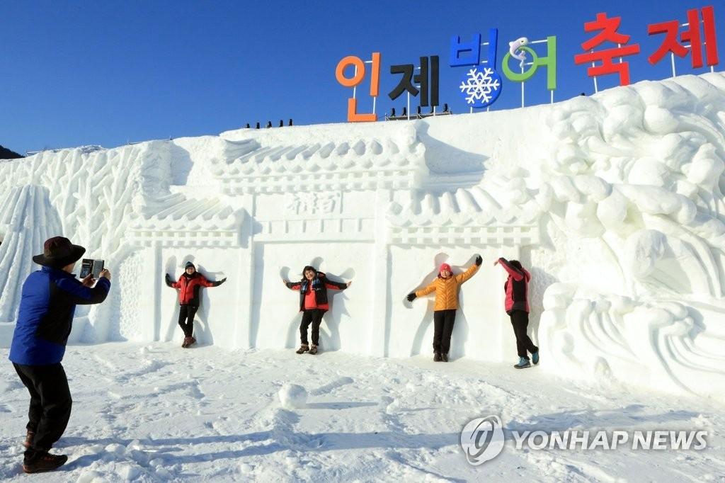1月27日,江原道麟蹄郡,游客们在活动现场合影留念。(韩联社)