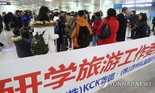 1月30日下午,在济州国际机场,64人组成的中国研学旅行团在入境后清点人数准备出发。(韩联社)