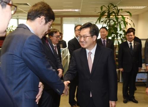 2月1日,在大韩商会北京办事处,韩国经济副总理兼企划财政部长官金东兖(右)与韩国企业家握手互致问候。(韩联社/企划财政部提供)