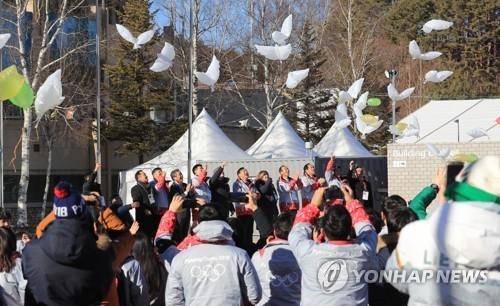 2月1日,在平昌运动员村,出席开村仪式的嘉宾放飞和平鸽气球。(韩联社)