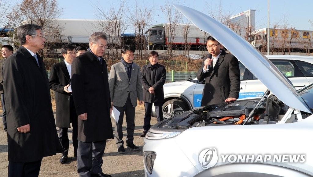 """2月2日上午,韩国总统文在寅试乘现代汽车研发的自动驾驶氢燃料电池汽车""""NEXO""""。图为文在寅(前排右二)听取现代汽车自动驾驶车研发组李振宇常务(前排右一)介绍。(韩联社)"""