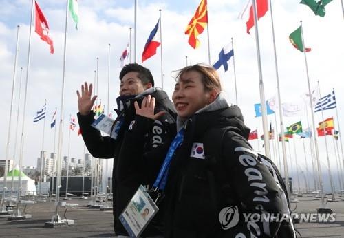 2月4日,在江陵运动员村内国旗广场,韩国花滑双人滑搭档甘强灿(左)和金奎訚向媒体记者招手致意。(韩联社)