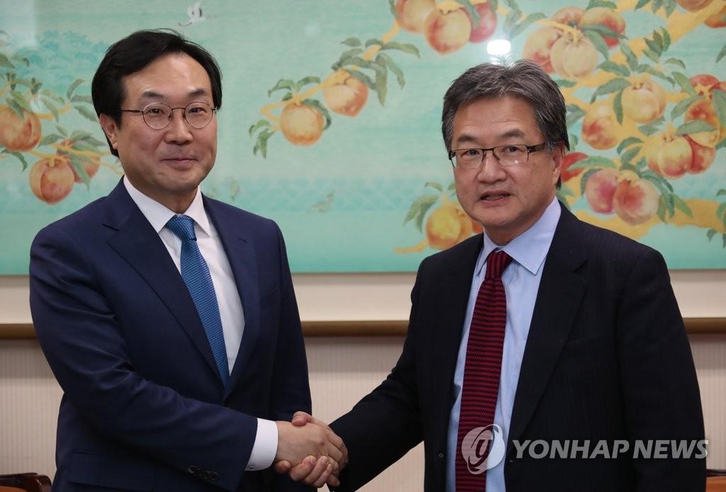 2月5日,在首尔外交部大楼,韩半岛和平交涉本部长李度勋(左)同美国国务院对朝政策特别代表约瑟夫·尹会谈前握手合影。(韩联社)