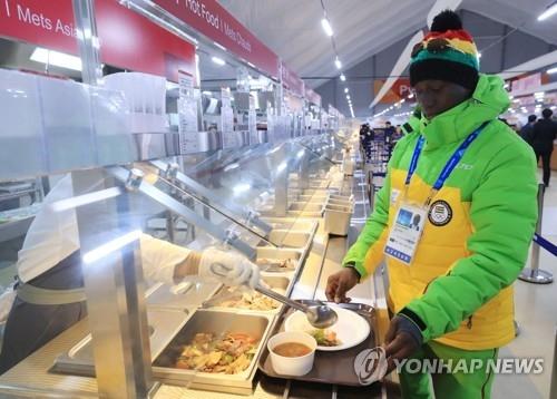 一名多哥共和国体育代表团的有关人士在取餐。(韩联社)