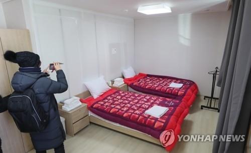 一名记者在参观运动员宿舍的样房。(韩联社)