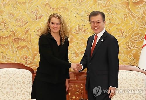 2月7日上午,在青瓦台,韩国总统文在寅(右)与加拿大总督朱莉·佩耶特握手合影。(韩联社)