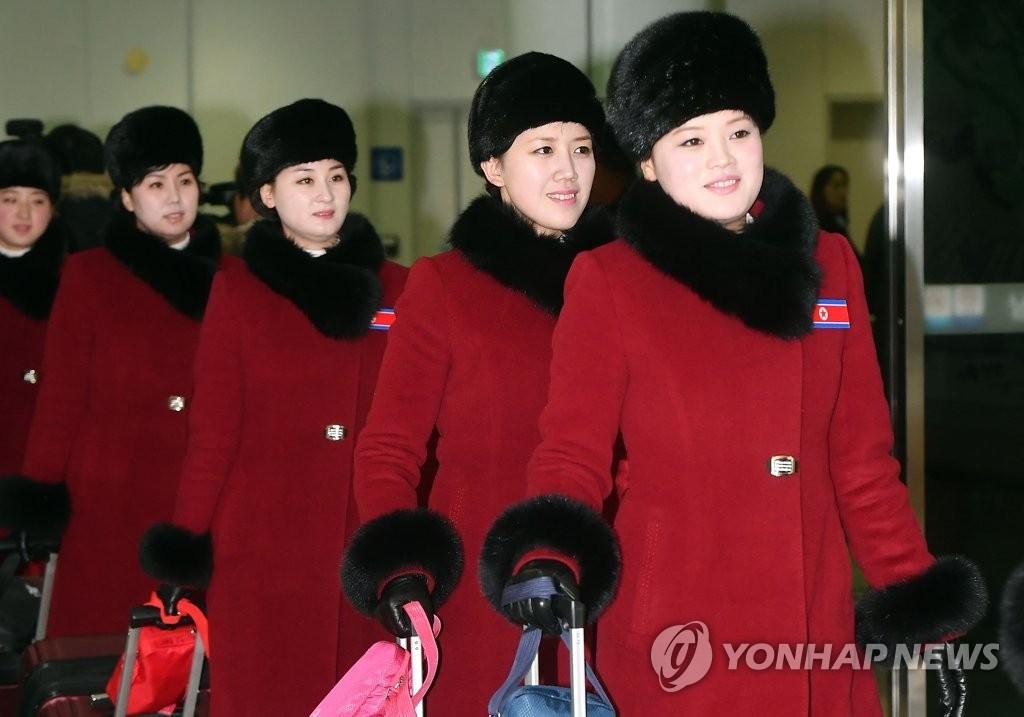 2月7日上午,在京畿道坡州市都罗山南北出入境事务所(CIQ),身着红衣,胸戴朝鲜国旗徽章的朝鲜拉拉队成员走入韩国境内。(韩联社/联合采访团)