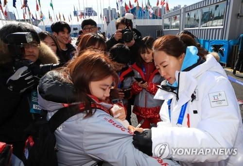 """2月7日上午,在江陵运动员村,韩国女子速滑选手李相花在韩国选手入村仪式上为志愿者签名。韩国代表团人数创历届冬奥会之最,目标是""""8-4-8-4"""",即争取8金4银8铜共20枚奖牌,综合排名第4。(韩联社)"""