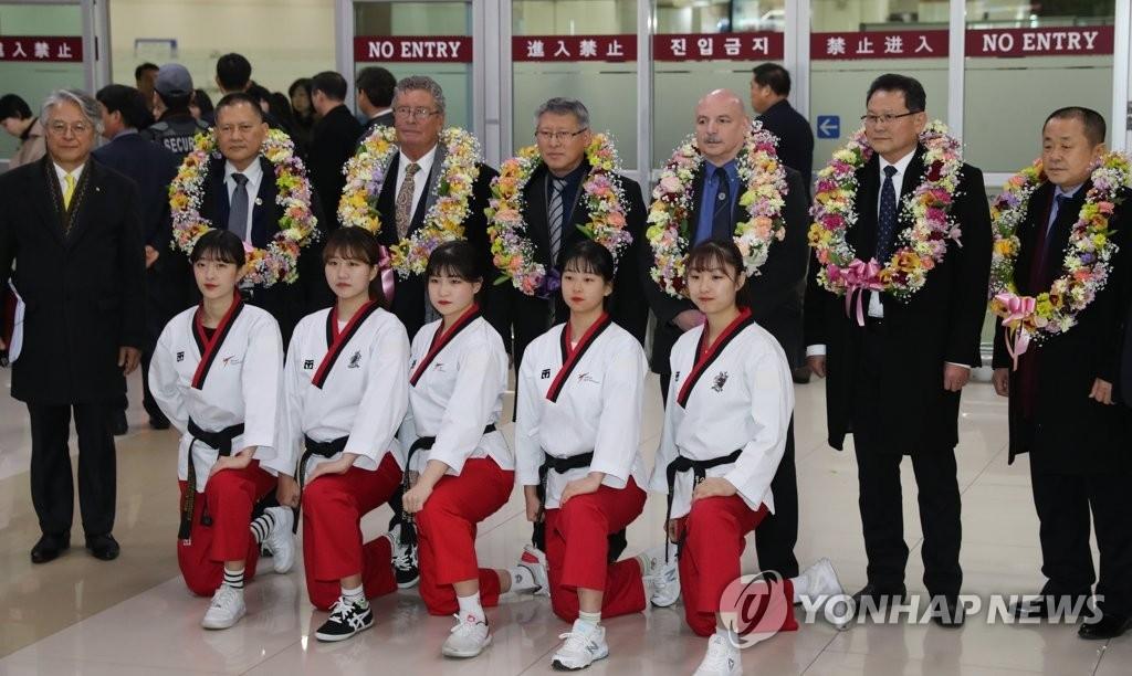 2月7日下午,在金浦机场,国际跆拳道联盟(ITF)总裁李勇鲜等ITF主要负责人一行六人入境韩国并同前往接机的世界跆拳道联盟(WT)大学生示范团合影。(韩联社)