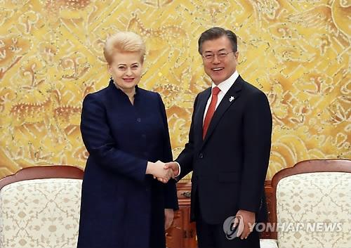 2月7日下午,在青瓦台,韩国总统文在寅(右)与立陶宛总统达利娅·格里包斯凯特举行会谈。图为双方在会谈前握手合影。(韩联社)