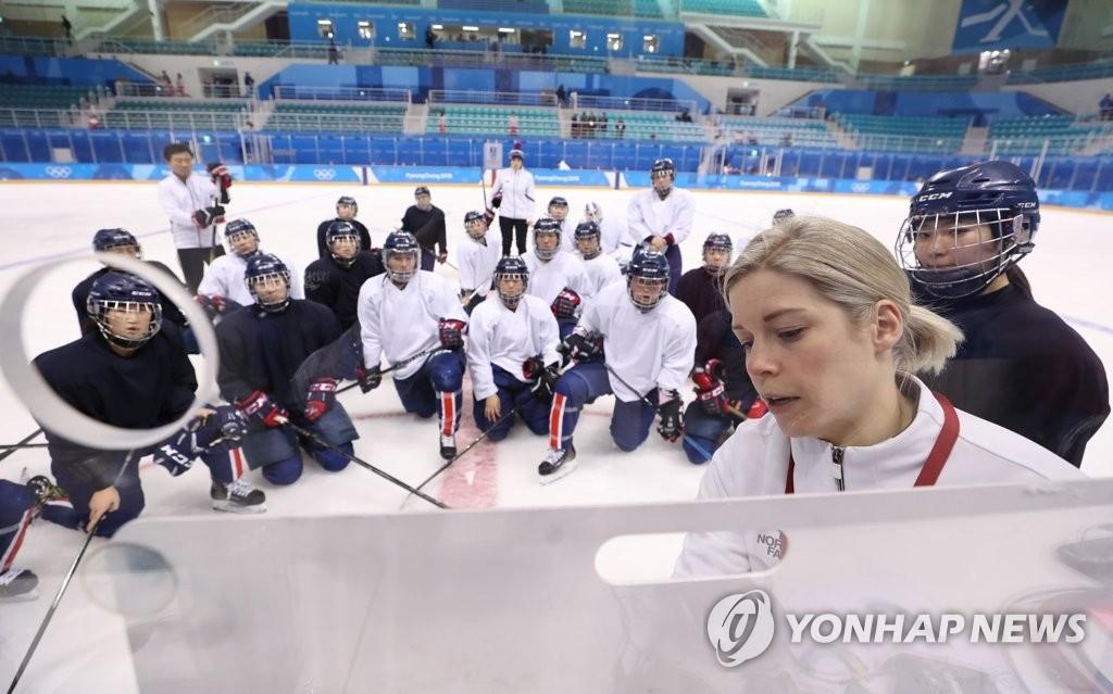2月7日下午,在江原道江陵市关东冰球中心,韩朝女子冰球联队主教练萨拉·穆雷(右一)向参加训练的韩朝联队队员们说明战术。(韩联社)