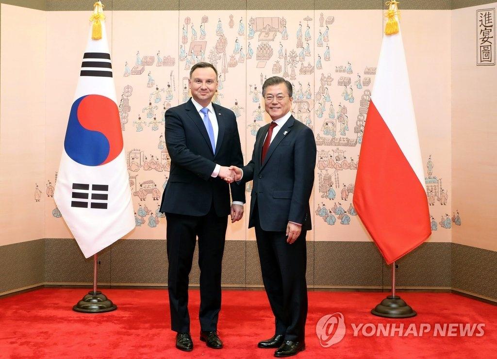 2月8日,在青瓦台,韩国总统文在寅(右)会见波兰总统安杰伊·杜达,并握手合影。(韩联社)