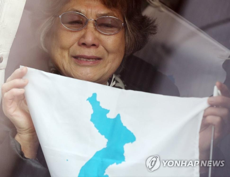2月8日,在金浦机场,由旅日朝鲜人总联合会会员组成的平昌冬奥会拉拉队成员抵韩。图为拉拉队一成员在机场巴士上手持韩半岛旗向记者致意。(韩联社)