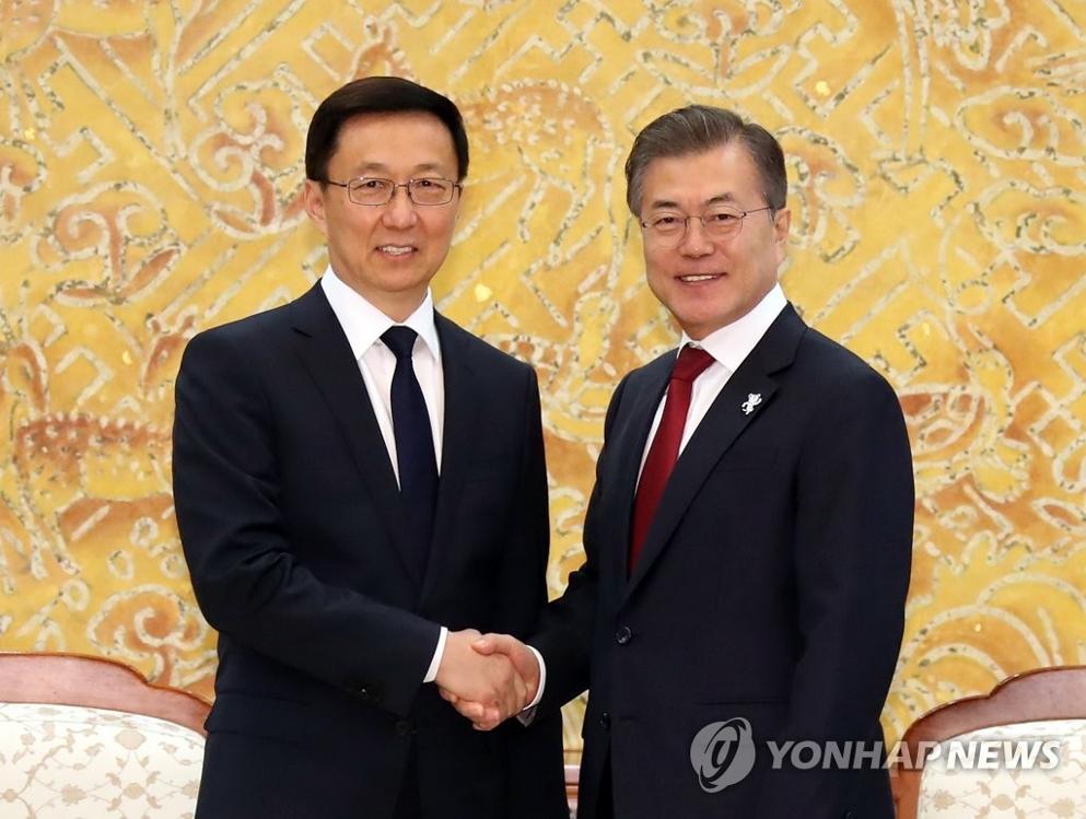 2月8日,在青瓦台,韩国总统文在寅(右)会见中共中央政治局常委韩正。图为双方握手合影。(韩联社)