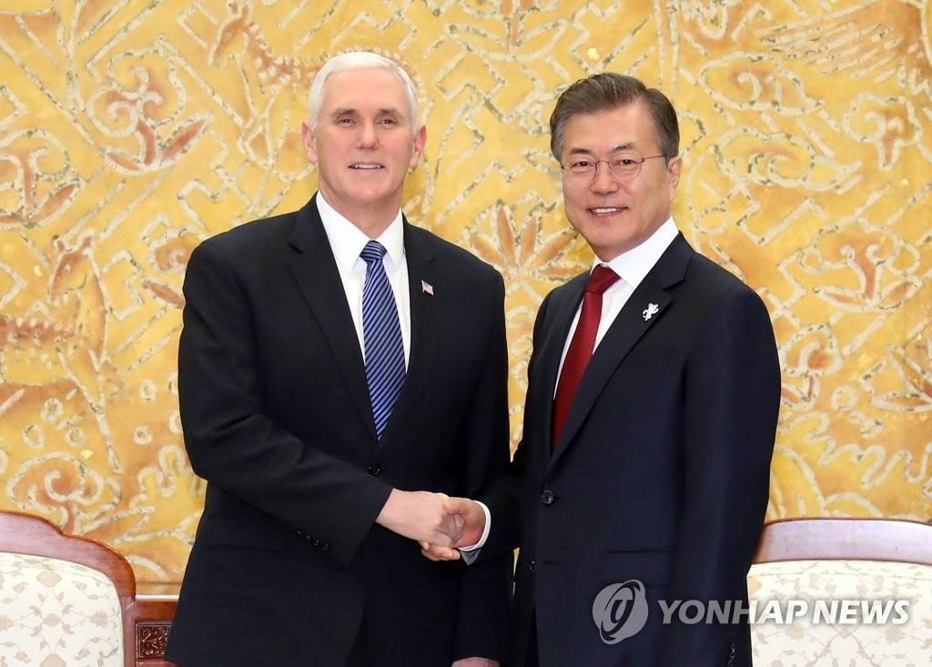 2月8日,在青瓦台,韩国总统文在寅(右)会见美国冬奥代表团团长、副总统迈克·彭斯,并握手合影。(韩联社)