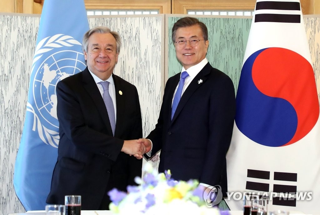 2月9日,在江原道江陵吉马凯酒店,韩国总统文在寅(右)同联合国秘书长安东尼奥·古特雷斯举行午餐会谈前握手合影。(韩联社)