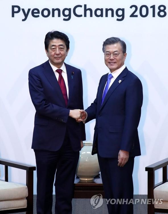 2月9日,在江原道龙平度假村,韩国总统文在寅(右)在欢迎招待会上同到访的日本首相安倍晋三握手。(韩联社)