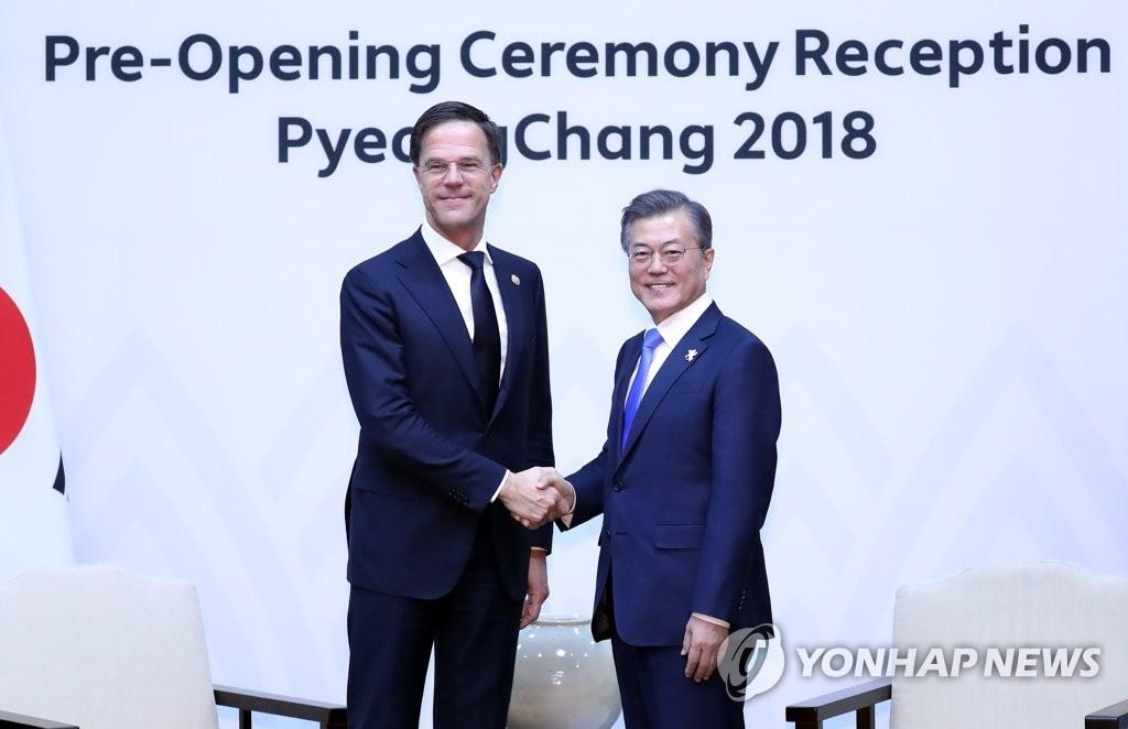 2月9日下午,在江原道龙平度假村,韩国总统文在寅(右)同荷兰首相马克·吕特举行会谈前握手合影。(韩联社)