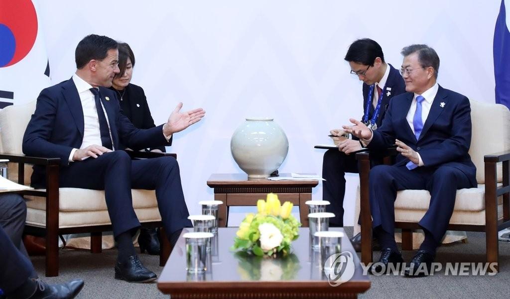 2月9日下午,在江原道龙平度假村,韩国总统文在寅(右)同荷兰首相马克·吕特举行会谈。(韩联社)