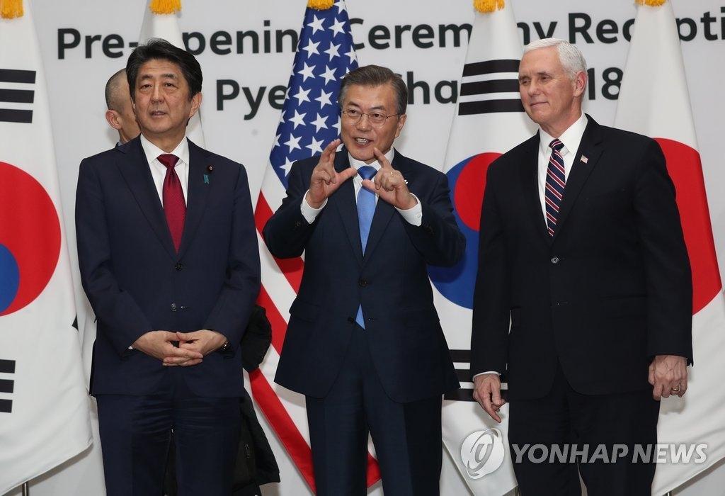 2月9日下午,在平昌,韩国总统文在寅(中)同日本首相安倍晋三(左)、美国副总统彭斯在各国领导人招待会上合影。(韩联社)