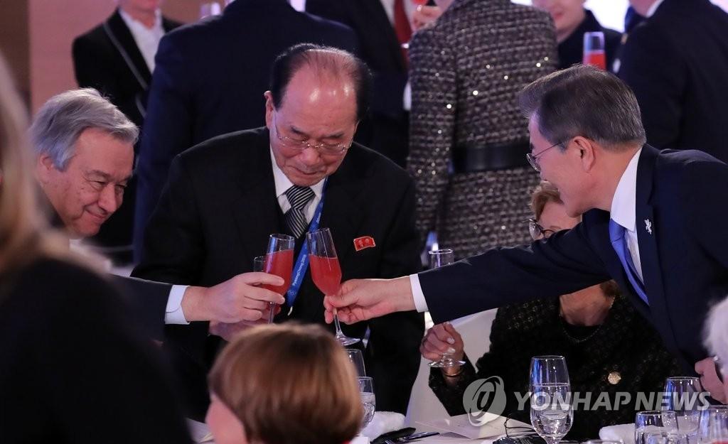 2月9日下午,在平昌,韩国总统文在寅(右)同朝鲜最高人民会议常任委员会委员长金永南(左)在各国领导人招待会上举杯致意。(韩联社)