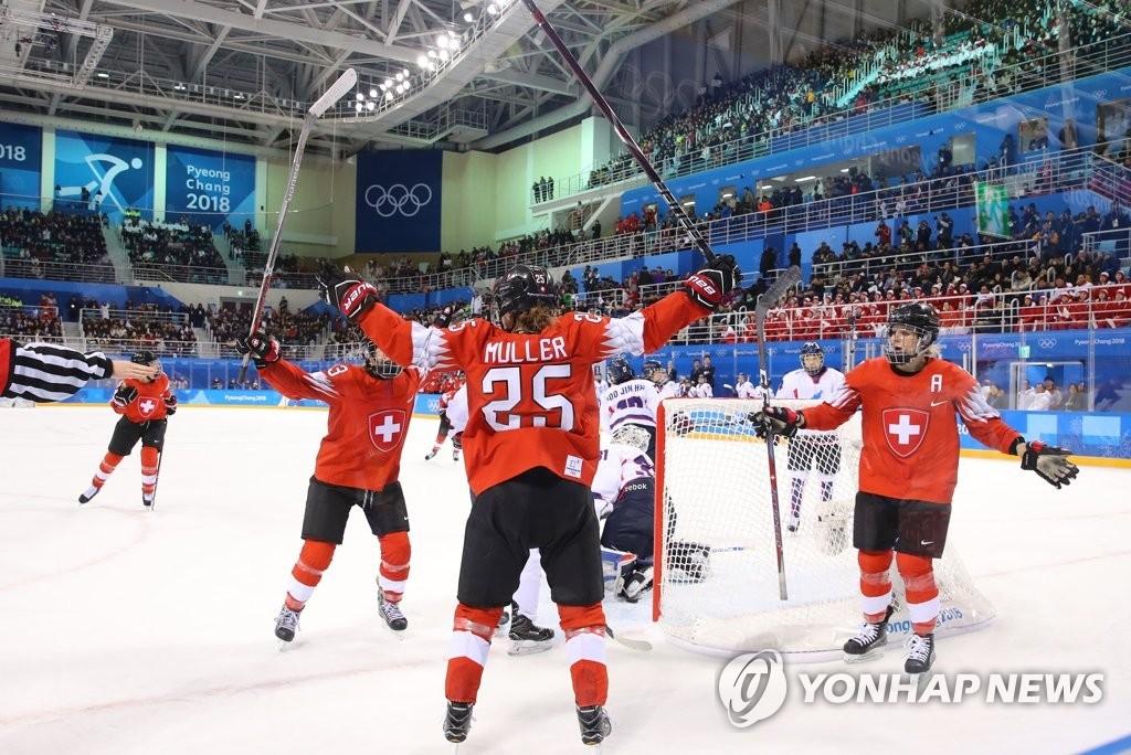 2月10日下午,在江陵关东冰球中心,韩朝女子冰球联队对阵瑞士队,图为瑞士队(红衣)进球后欢呼。(韩联社)