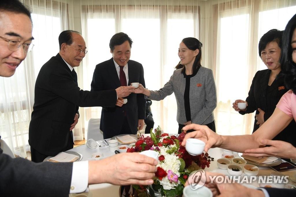 2月11日,在华克山庄酒店,韩国总理李洛渊(中)与金与正(右二)等朝鲜冬奥高官团共进午餐。图为列席人士在席间举杯。(韩联社)
