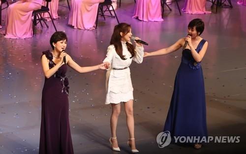 2月11日下午7时,在首尔国立中央剧场,少女时代徐玄(中)与朝鲜艺术团所属歌手合唱《我们的愿望》。(韩联社)