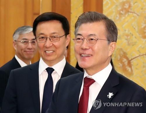 资料图片:2月8日,在青瓦台,韩国总统文在寅(右)接见了到访的中共中央政治局常委韩正(中)。(韩联社)