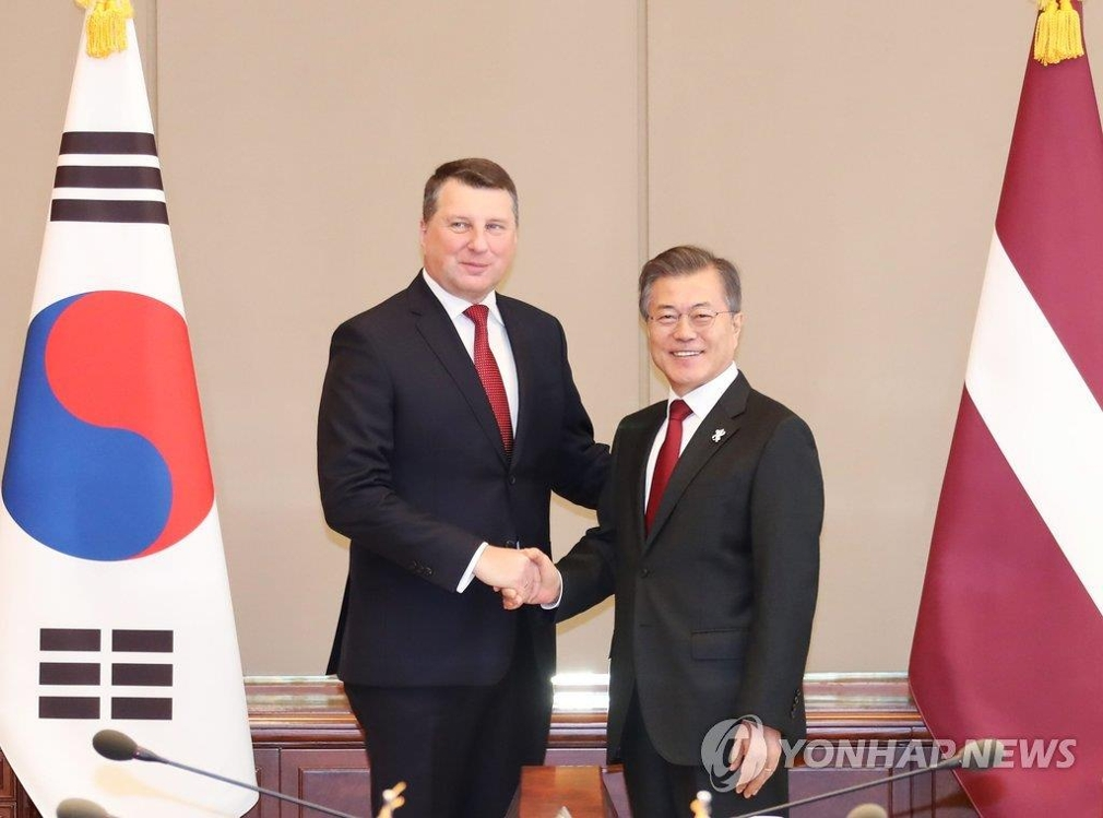 2月13日下午,在韩国青瓦台,总统文在寅(右)与到访的拉脱维亚总统韦约尼斯举行会谈,两位领导人在会谈开始前握手合影留念。(韩联社)