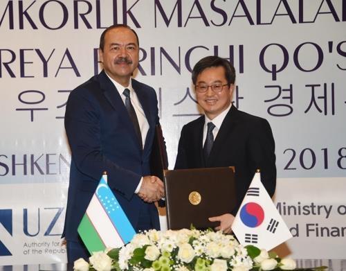 韩国经济副总理金东兖(右)和乌兹别克斯坦总理阿里波夫握手合影。(韩联社/企划财政部提供)
