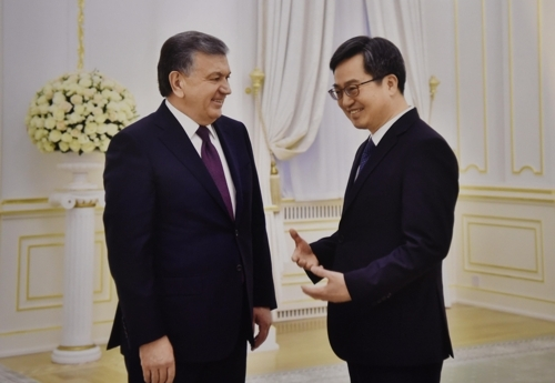 金东兖(右)拜会米尔济约耶夫。(韩联社/韩国企划财政部)