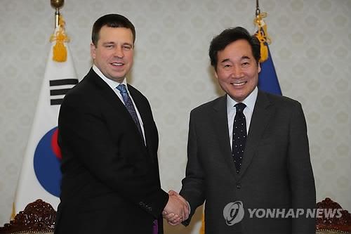 2月14日上午,在首尔中央政府大楼,韩国国务总理李洛渊(右)与到访的爱沙尼亚总理于里·拉塔斯握手。(韩联社)